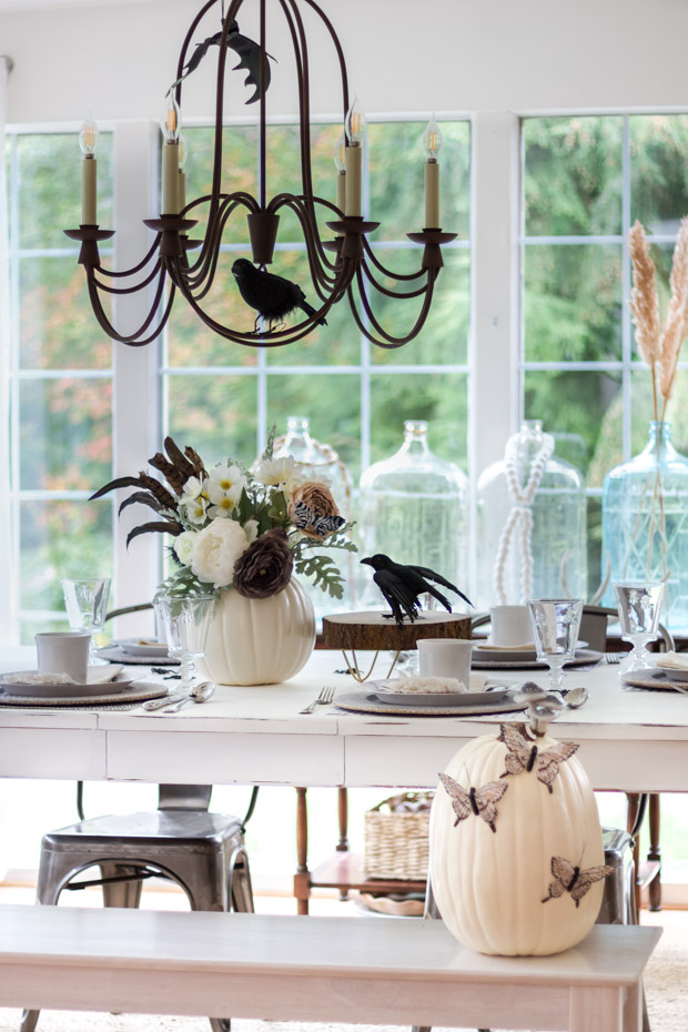 White, brown and green floral arrangement, black crow all on dining table.