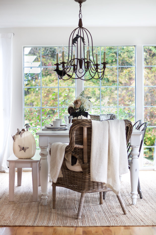 Wicker dining room chair with a white blanket on it.