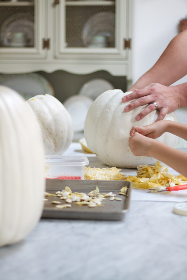 Carving white pumpkins on table.