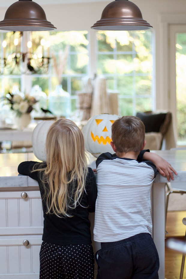 Two kids looking at the carved pumpkins on the counter.