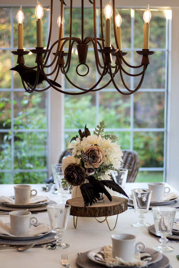 Chandelier above the table lit up with flowers on the table.