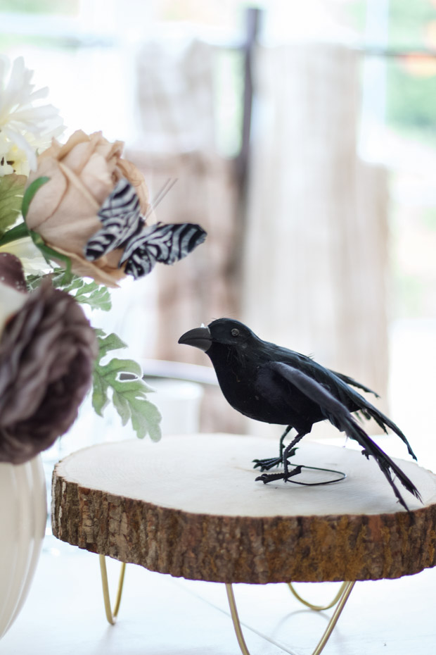 Black crow on a wooden pedestal on the dining table.