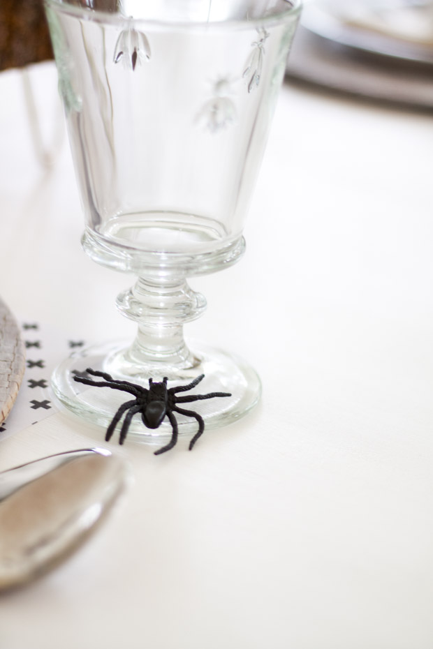 A black spider beside the drinking glass on table.