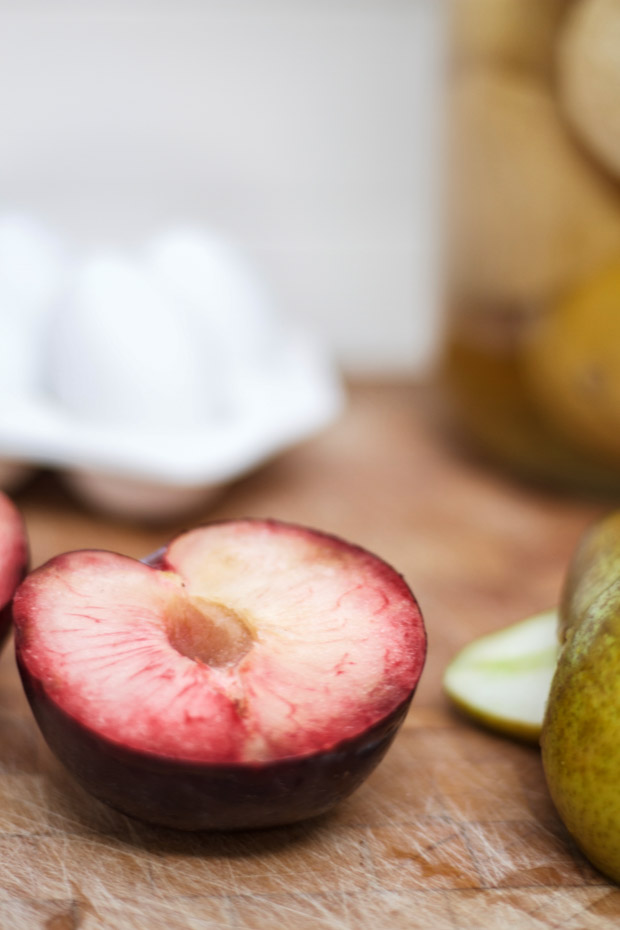 A plum cut in half on a cutting board.