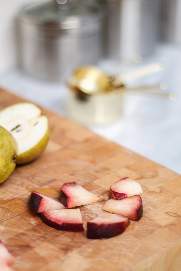 Plums cut into quarters on a cutting board with half a pear in the background.