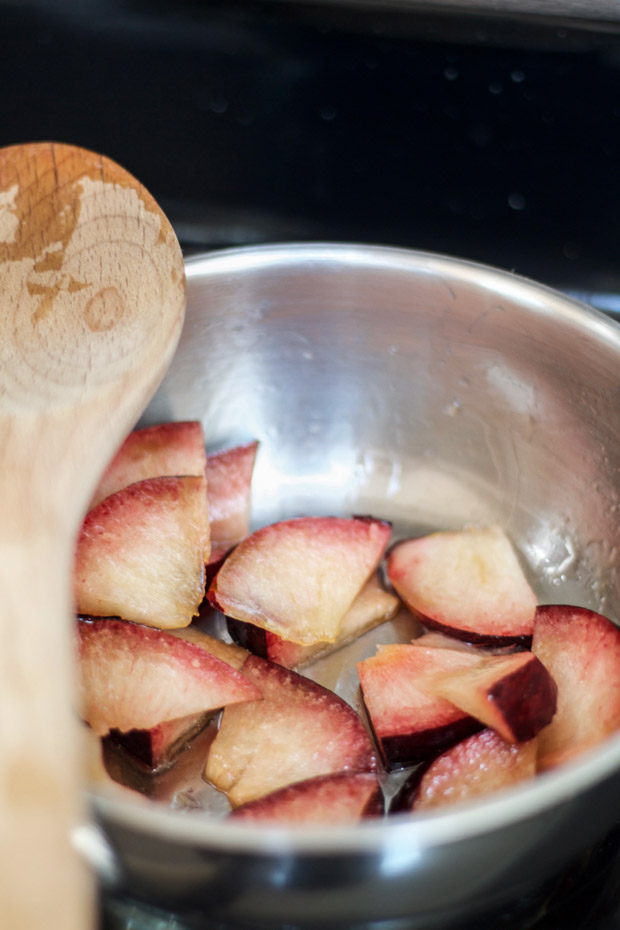 The plums in a steel bowl on the stove.