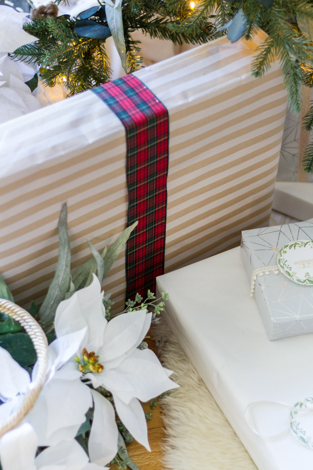 A wrapped present with a red tartan ribbon around it.