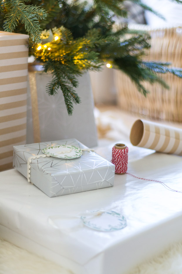 A large present on the carpet and a smaller present on top of it with a spool of twine beside it.
