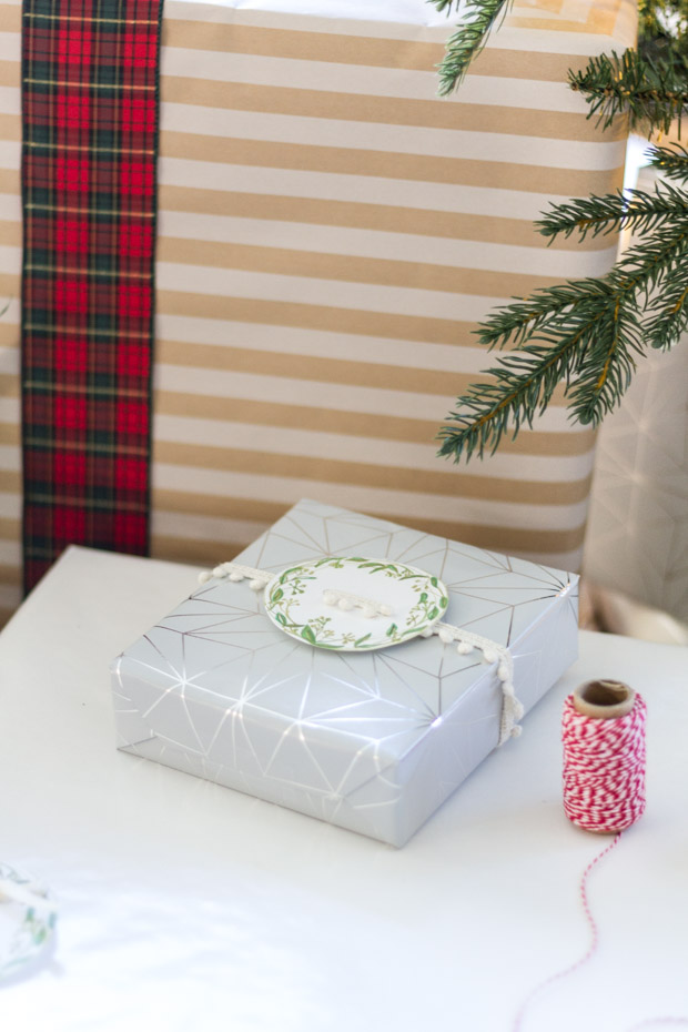 A present in a silver wrapping with the greenery tag on it.