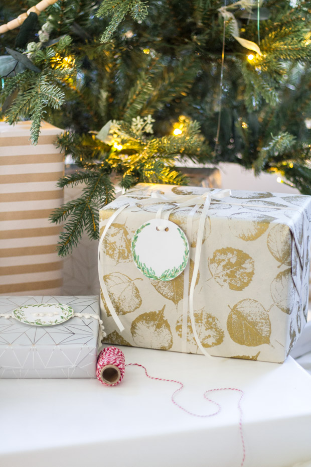 A large wrapped present in gold leaf paper and the greenery label on it.