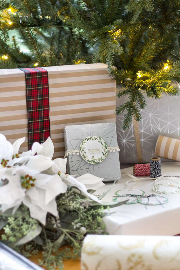 Christmas presents under the tree and the greenery gift tag on them.