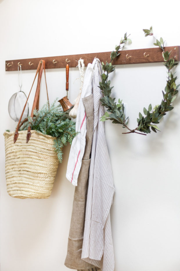 Laurel wreath on hooks with a basket filled with herbs.
