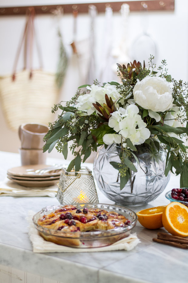 A clear vase with white flowers and the cinnamon buns baked in front of it.