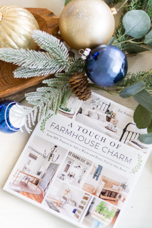 A touch of farmhouse charm book on the counter surrounded by Christmas ornaments.
