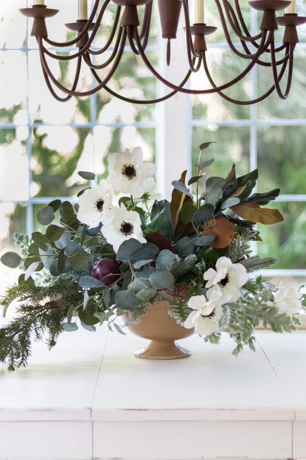 The floral arrangement on the table underneath a metal chandelier.