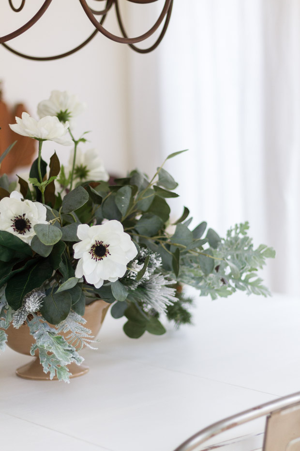 The white flowers and black centers, and eucalyptus in the arrangement on the table.