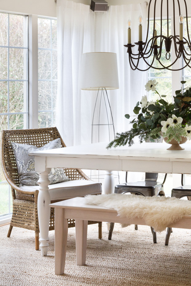 The floral arrangement on the wooden table with a faux fur on the bench.