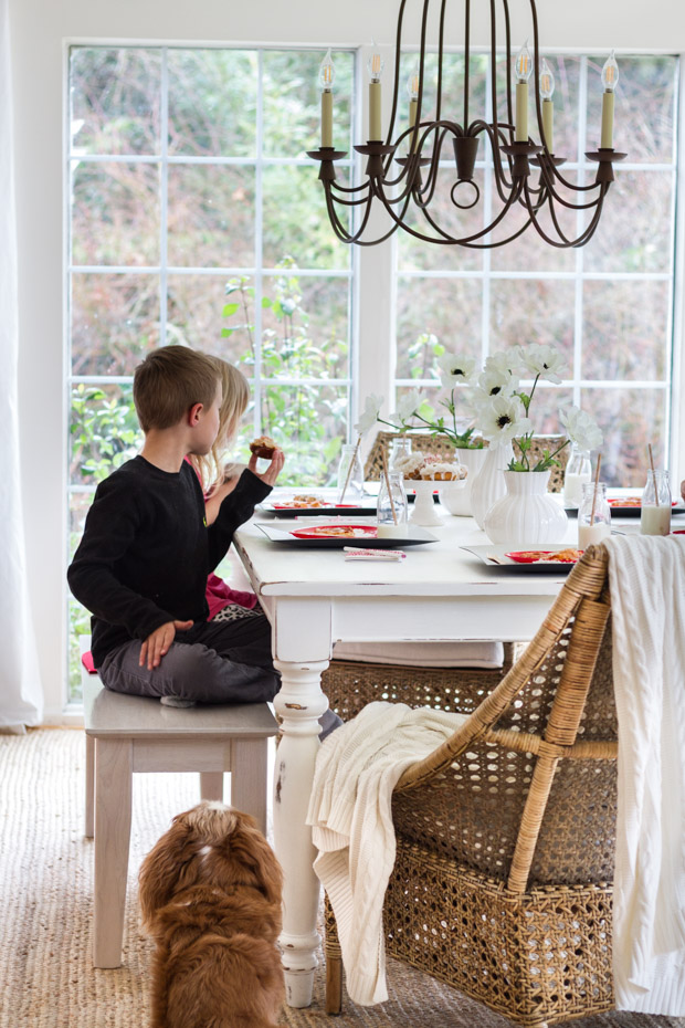 Kid's at the table eating with a little dog staring at them.