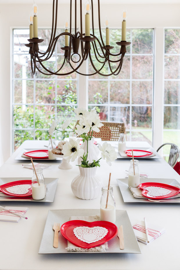 Red heart plates on the table with a metal chandelier hanging above the table.