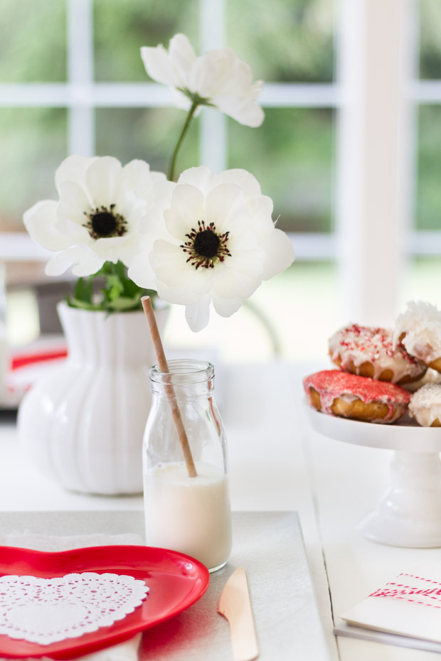 Glasses of milk with straws in them beside the vase with white flowers on the table.