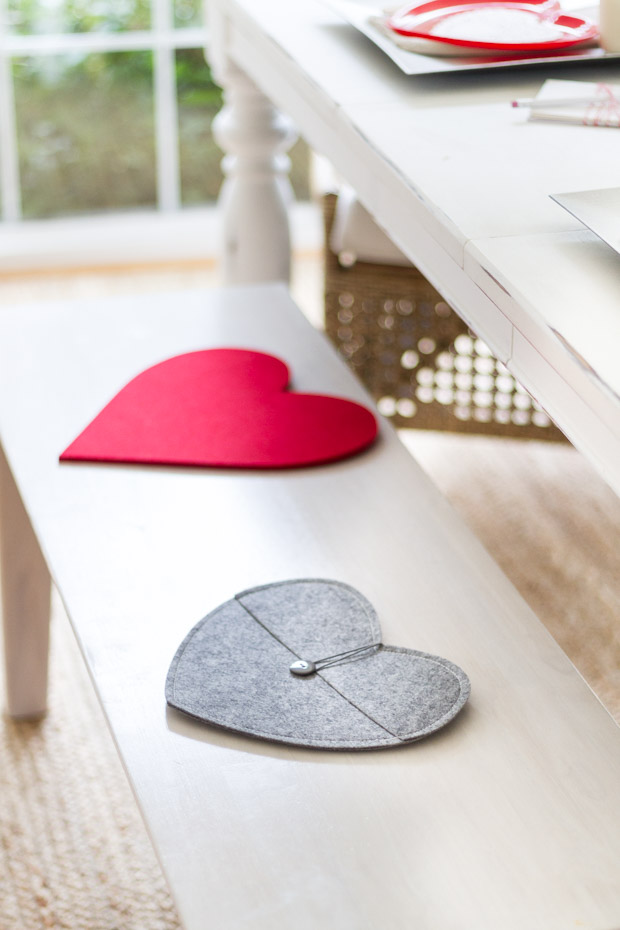 Red, gray fabric hearts on a wooden bench.