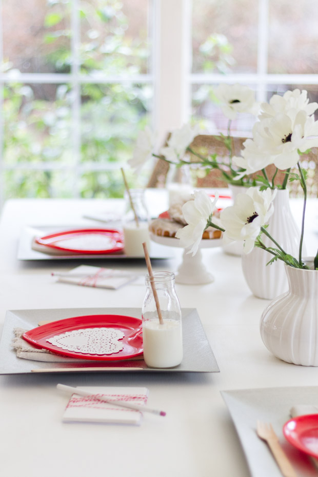 Red heart paper plates with glasses of milk beside them on the table.