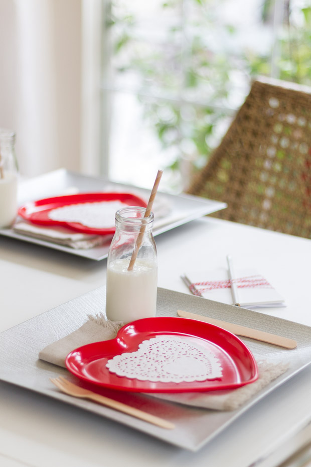 Red paper plate with a white doily on the table.