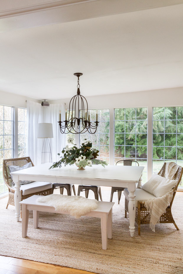 A wide shot of the dining room table with a chandelier above the table.