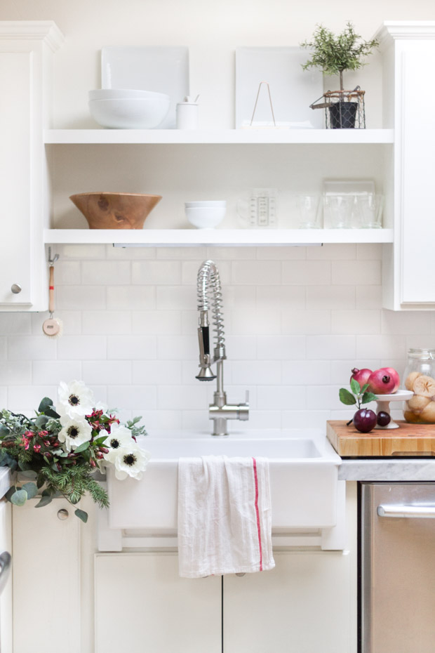 The kitchen sink, with open shelves above the sink and flowers beside it lying on the counter.