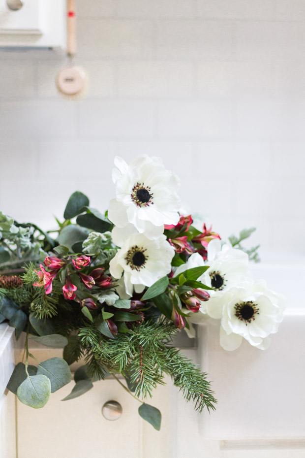 The white, pink flowers and greenery on the kitchen counter by the sink.