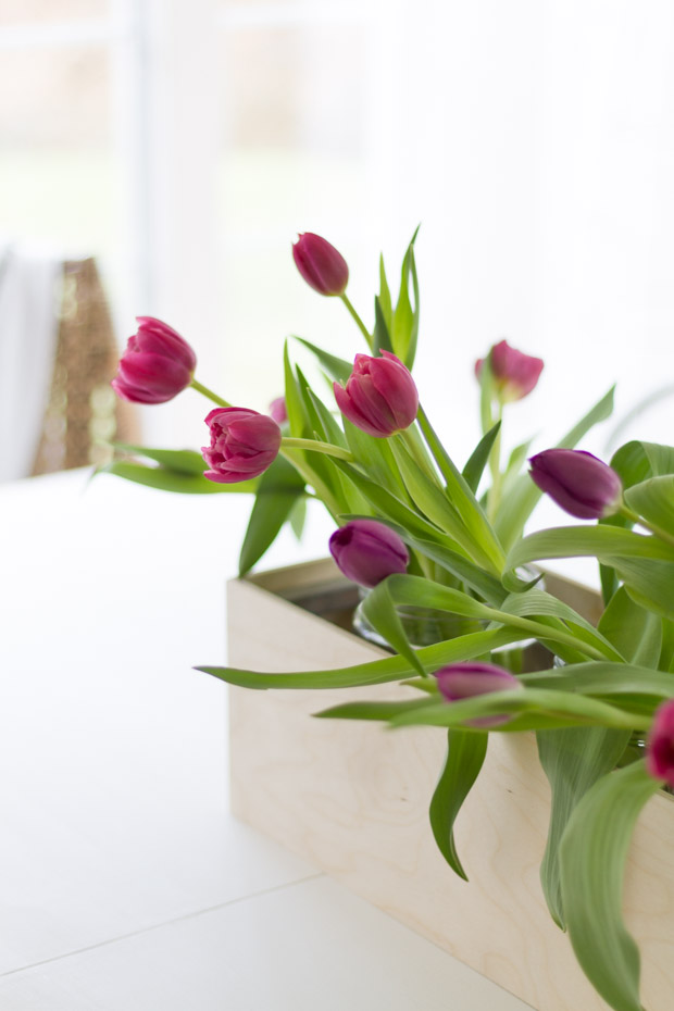 Pink tulips with green stems in vases on the table.