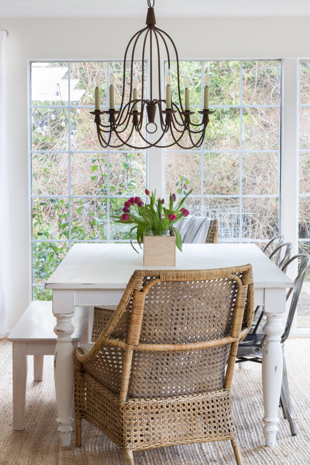 The dining room table with a wicker chair and a wrought iron chandelier.