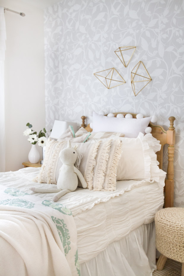 A childs bedroom with white and pink bedding and delicate finged pillow on the bed