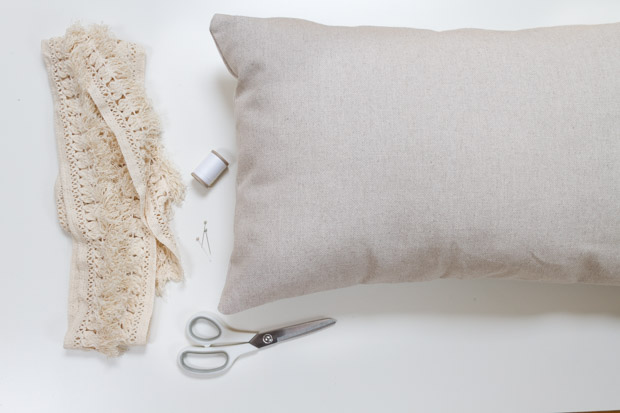 Scissors, white thread, fringe and a pillow laid out.