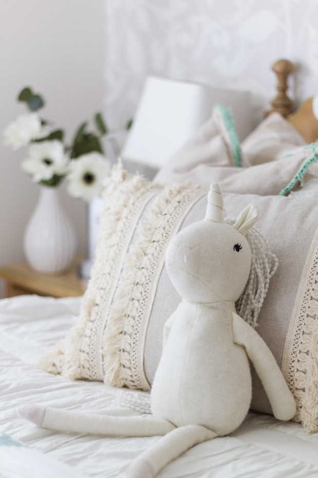 A white unicorn stuffy leaning against the pillow.