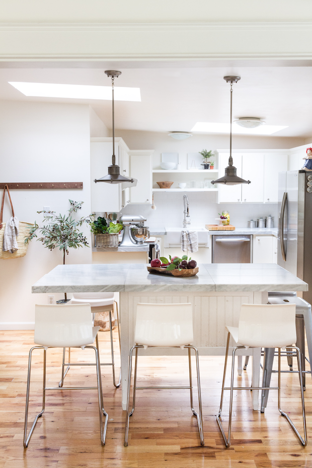 White kitchen with lights hanging over the kitchen island.