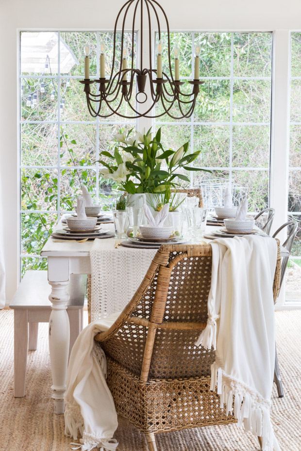 A wicker chair with a white blanket on the chair.