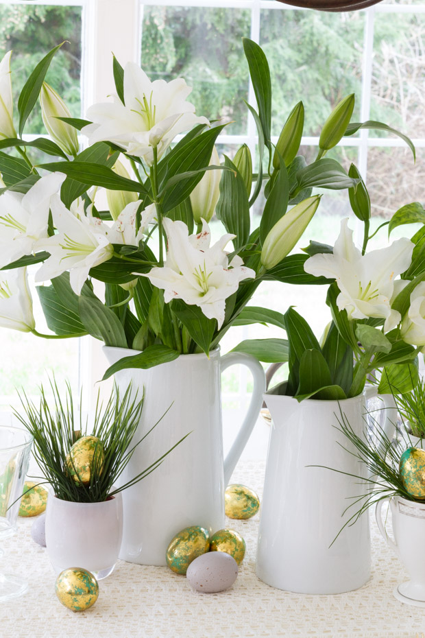 White lillies in white vases on the table with gold Easter eggs.