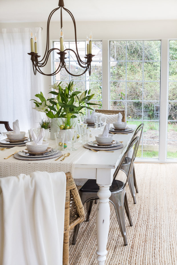 A large floor to ceiling window by the table decorated for Easter.