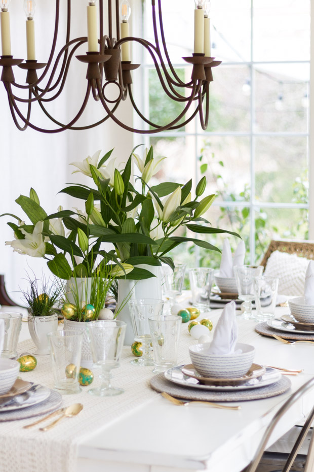 A mostly white table and table cloth, and a chandelier over the table.