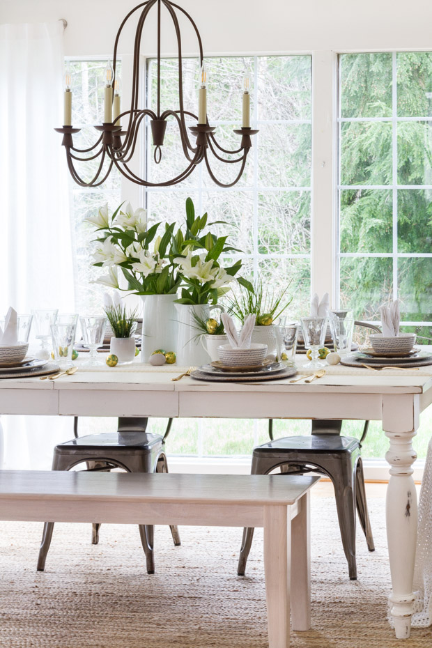 A white table with white flowers on the table and a chandelier over top the table.