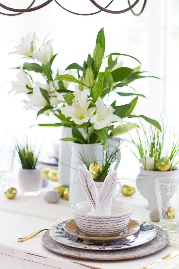 White dishes with patterns and Lillys on the table in a white vase.
