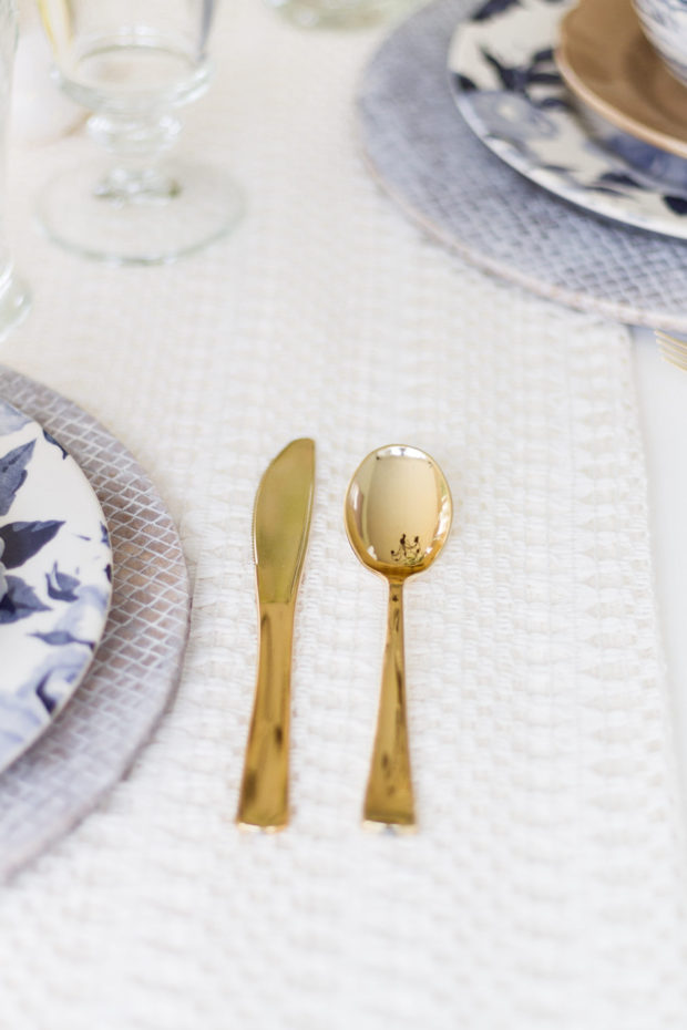 A gold spoon and knife on the table.
