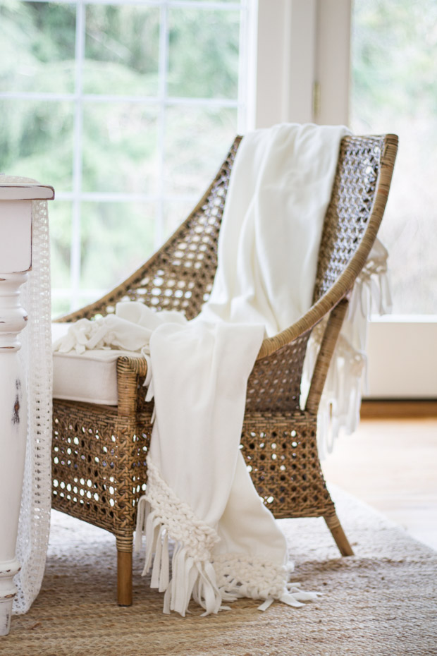 A white blanket on the wicker chair at the head of the table.