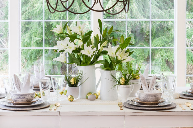 The table set for Easter with white flowers and gold Easter eggs.