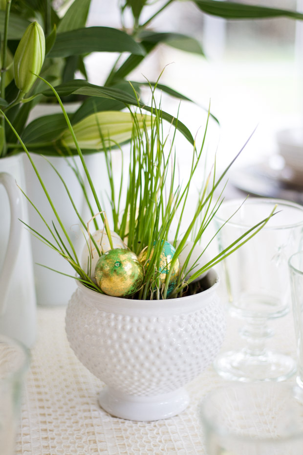 A white vase with green ornamental grass in it.