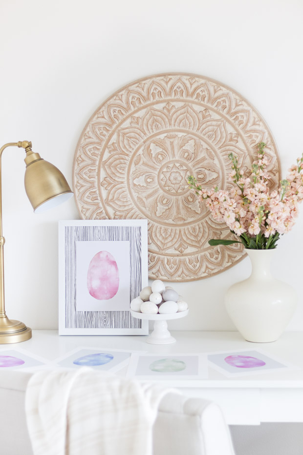 The framed printable on the desk beside the white vase and a large picture on the wall.