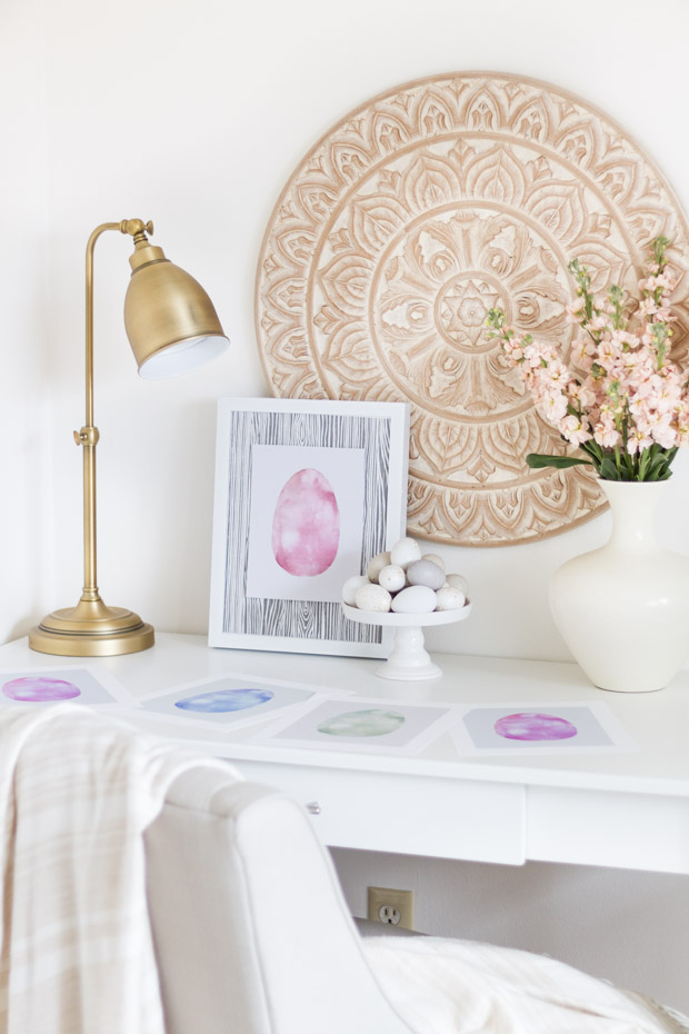 A white desk with a watercolor Easter egg printable that is framed on the desk.