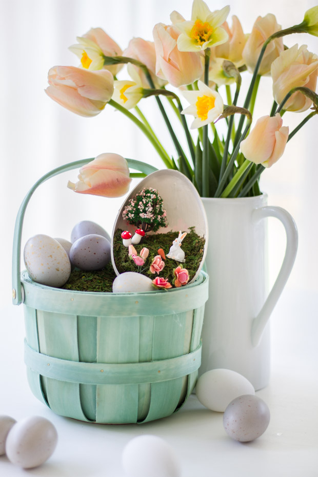 The light green decorated Easter Basket beside a white jug full of flowers.
