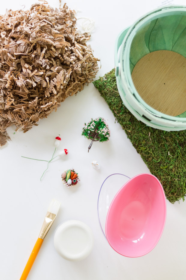 A basket, moss, a plastic egg, a brush and little ornaments on the table ready to go.